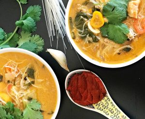 spicy thai soup with spoon of red curry paste, garlic cloves, and cilantro garnish
