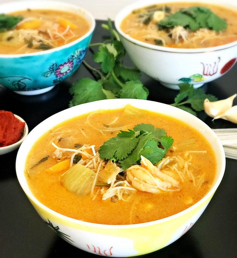 three bowls of spicy thai soup topped with cilantro