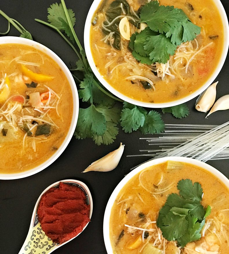 the bowls of spicy thai soup surrounded with cilantro, garlic cloves, red curry paste, and cilantro
