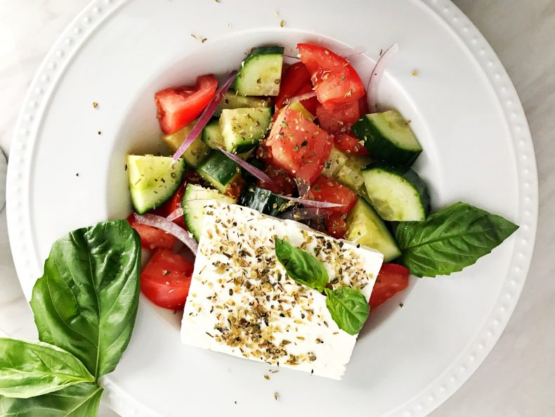 greek salad with block of feta and basil on top