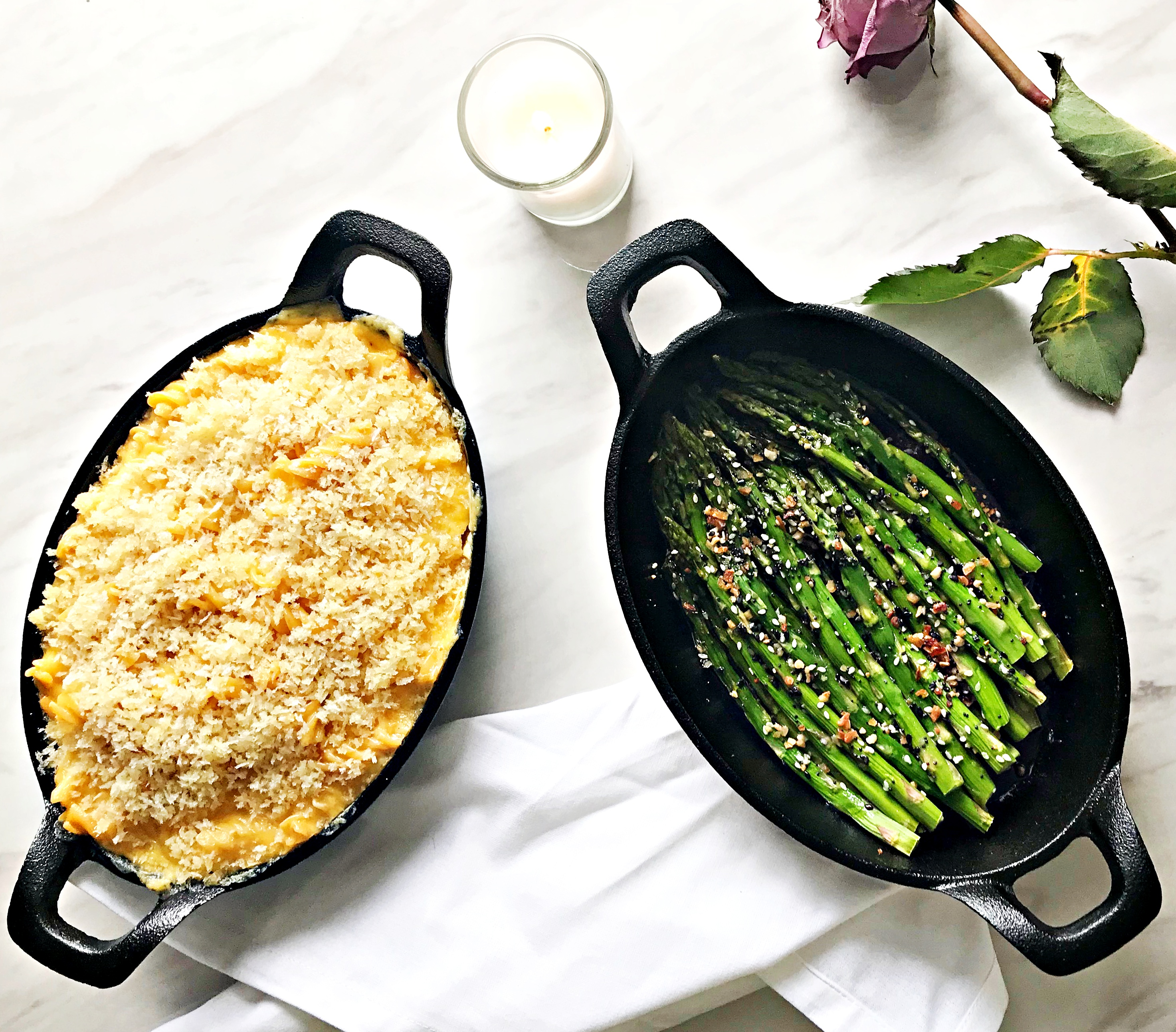 skillet with macaroni and cheese with skillet of seasoned asparagus