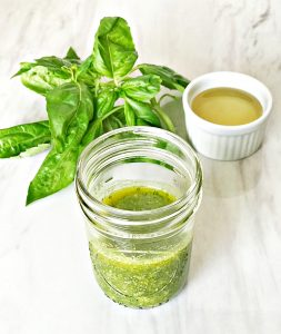 basil oil dressing in mason jar with a small cup of oil and bundle of basil