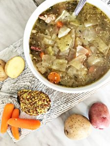 a bowl of irish soup on a wooden plank surrounded by carrots, potatoes, and whole seed mustard