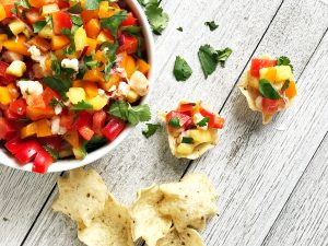 pineapple shrimp salsa in a white bowl with chips