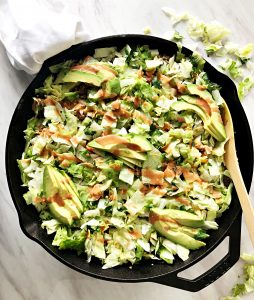 taco skillet topped with lettuce and avocados, wooden spoon on side