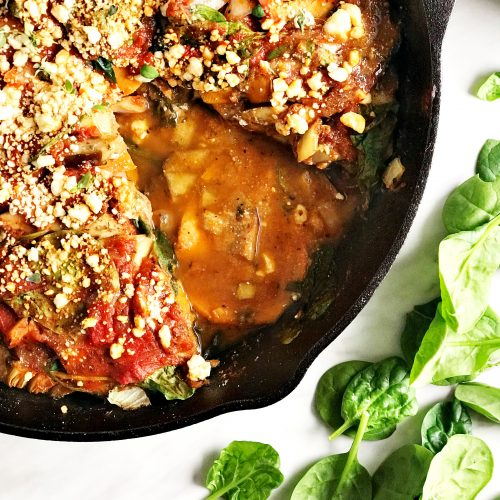 eggplant lasagna in a black skillet surrounded by green spinach