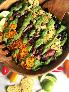 mexican steak salad with avocado cilantro dressing in large wooden bowl on white table