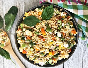 bowl of orzo salad on white wooden table