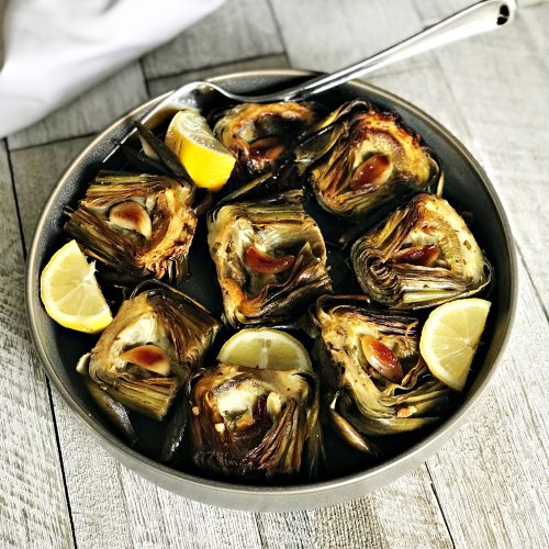 bowl full of roasted artichokes on white wooden table